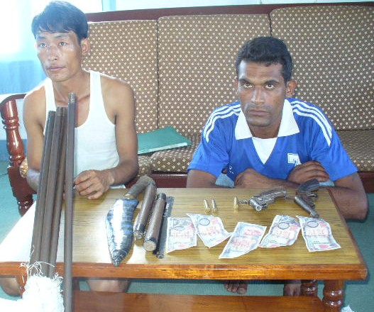 Bibek Limbu (right) and Prem Bista with seized weapons and fake notes